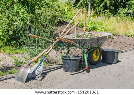 Wheelbarrow with gardening tools - stock photo
