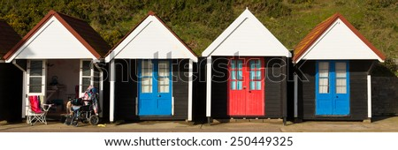 Wheelchair and colourful beach huts with blue and red doors in a row traditional English structure and shelter found at the seaside panorama - stock photo
