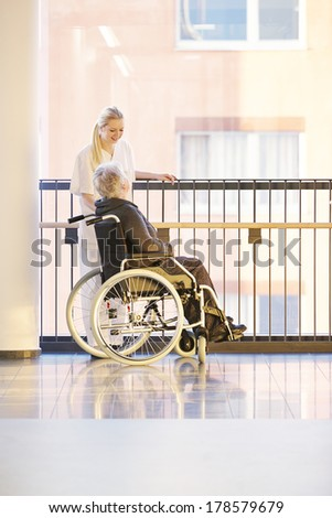 Wheelchair and patient in hospital with nurse talking - stock photo