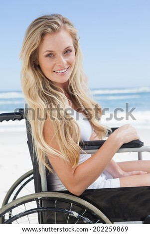 Wheelchair bound blonde smiling at the camera on the beach on a sunny day - stock photo