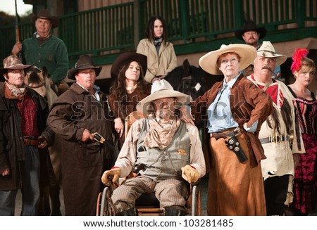 Wheelchair bound cowboy with wife and old west era gang - stock photo