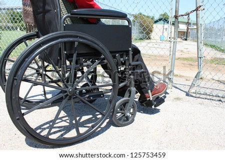 Wheelchair-bound person in front of a road block - stock photo