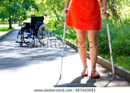 wheelchair (in focus) and woman (out of focus) practicing walking on crutches