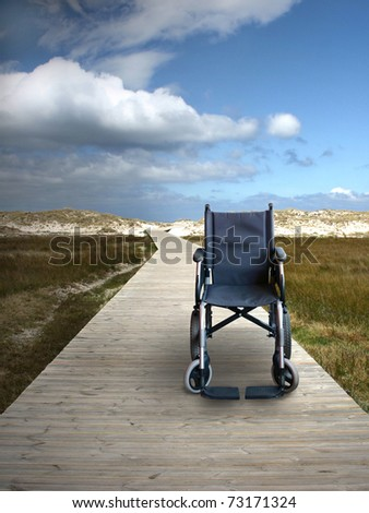 Wheelchair on a track to the beach - stock photo
