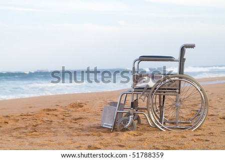 wheelchair on beach - stock photo
