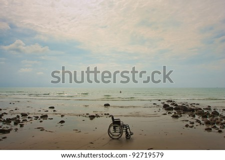 wheelchair on the beach - stock photo