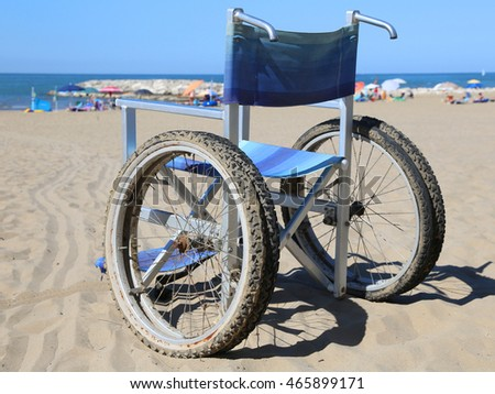 Wheelchair on the beach sand near the sea and many parasol in background
