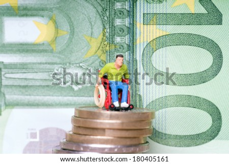 Wheelchair user on a stack of euro coins with euro banknote / Wheelchair user - stock photo