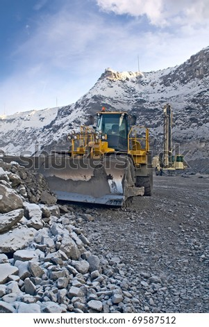 wheeled tractor and drilling rig in the workplace - stock photo