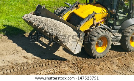 wheeled tractor loading the gravel - stock photo
