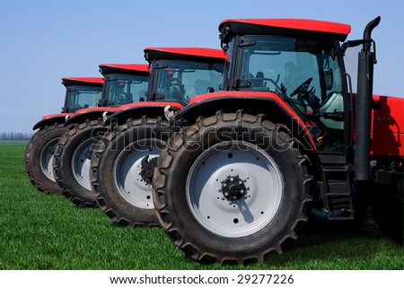 wheeled tractor on a green grass - stock photo