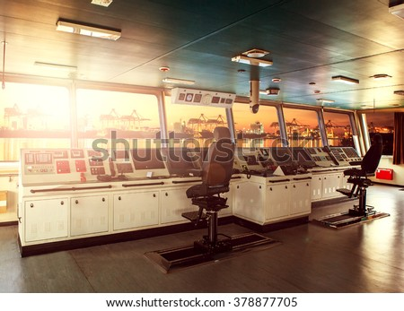 wheelhouse control board of modern industry ship approaching to harbor at night - stock photo