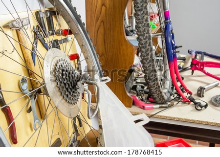 Wheels and bicycle parts over workshop table in the restoration process of a damaged bike - stock photo