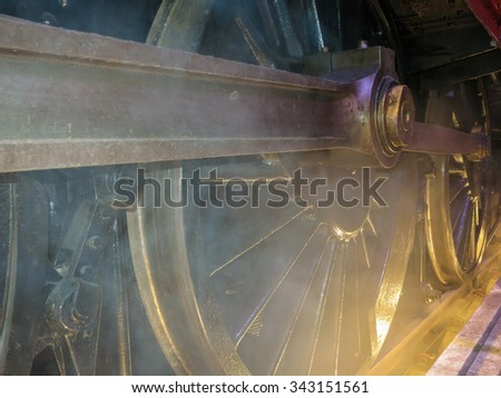 Wheels and steam of old locomotive, old train closeup.