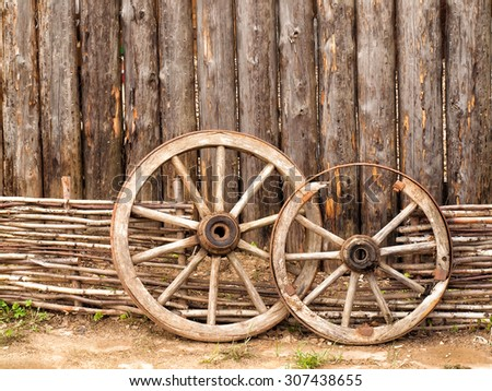 Wheels in the yard of wooden log house in Russian village in the middle Russia - stock photo