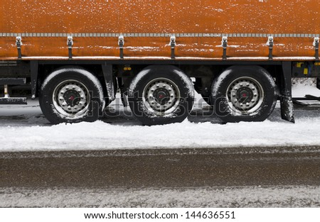 wheels of a parked trailer in winter - stock photo
