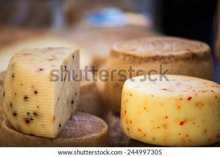 Wheels of cheese seasoned with herbs to sell on stall - stock photo