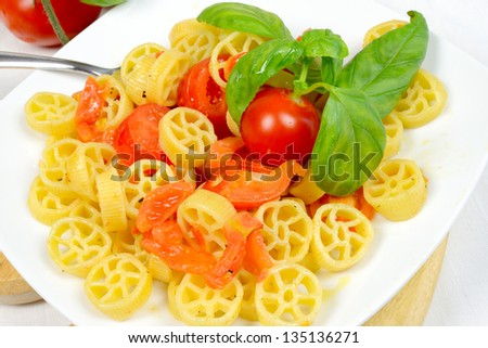 wheels of pasta with fresh tomatoes and basil oil