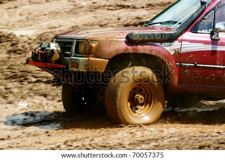 Wheels spinning on an off road vehicle as it skids across the mud - stock photo