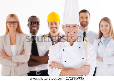 When I grow up I will be a chef. Confident male chef in uniform keeping arms crossed and smiling while group of people in different professions standing in the background - stock photo