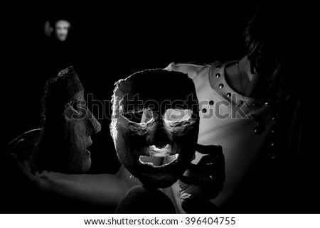 When the masks start to fall off 5. Low-key photography project with references and relations to the modern psychology and meanings of the masks. Girl playing with masks showing different emotions. - stock photo
