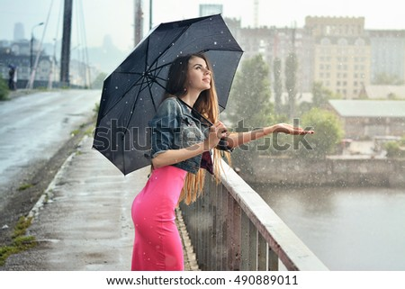 When the rain is over?  Cheerful girl with umbrella standing on the bridge in the rain.