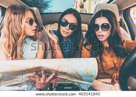 Where are we? Three beautiful young cheerful women looking confused and holding city map while sitting in car - stock photo