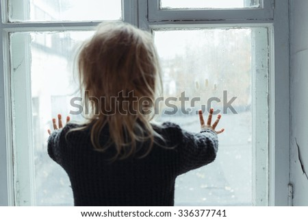 Where are you. Close up of hopeless little girl standing near window and holding her hands on the glass while waiting for parents - stock photo