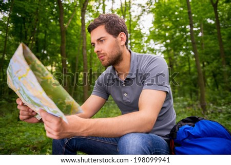 Where I am? Concentrated young man with examining map while sitting in a forest with backpack laying near him