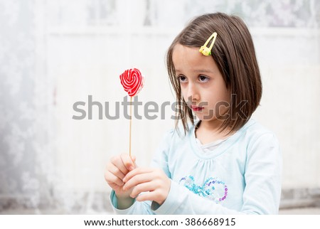 where is my lollipop, sad girl - stock photo