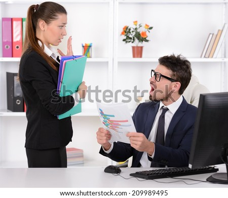 Where is the report? Stressed young businessman shouting at his secretary while sitting at his working place - stock photo