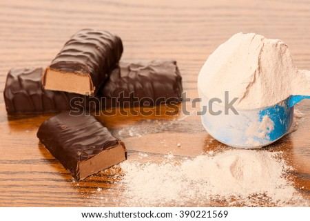 Whey protein powder in measuring scoop and chocolate protein bar on wooden background. - stock photo