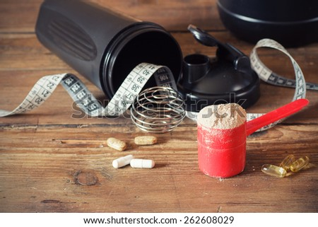 Whey protein powder in scoop with vitamins and plastic shaker on wooden background. Selective focus, shallow DOF - stock photo