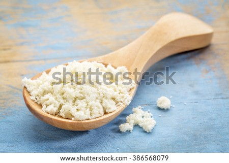whey protein powder on a wooden spoon against blue painted grunge wood - stock photo