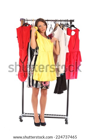 Which dress should I pick, young woman holding wear, studio - stock photo