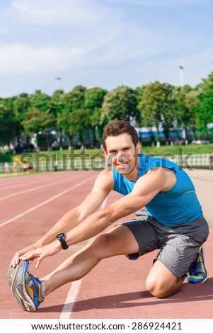 While exercising. Young attractive guy sitting on floor and leaning up to his feet - stock photo