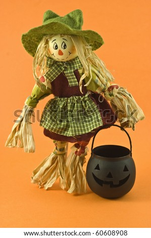 Whimsical corn husk farmer's wife doll with black pumpkin on orange background with copy space in vertical format - stock photo