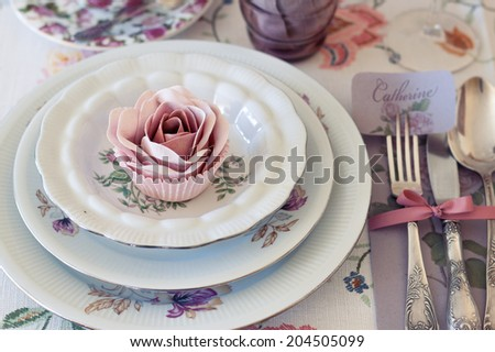Whimsical place setting with sugar rose cupcake on vintage china. Sweet and romantic detail of tea party table. Perfect for a DIY, vintage or farm wedding. Shallow depth of field. - stock photo