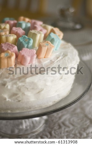 Whimsical White Frosted Cake with Flower Marshmallows on a Cake Plate - stock photo