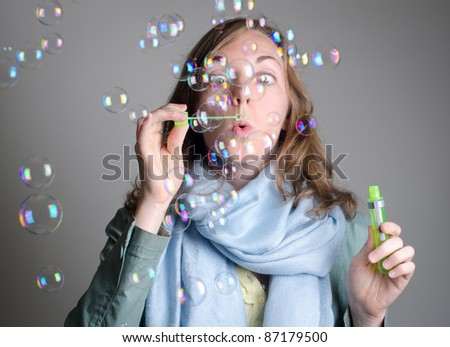 Whimsical woman blows rainbow bubbles