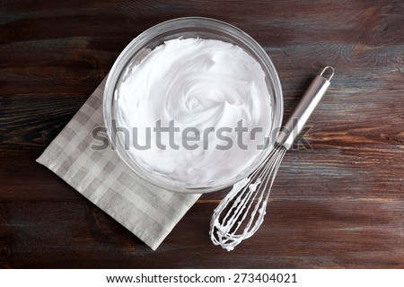 Whipped egg whites for cream on wooden table, top view - stock photo