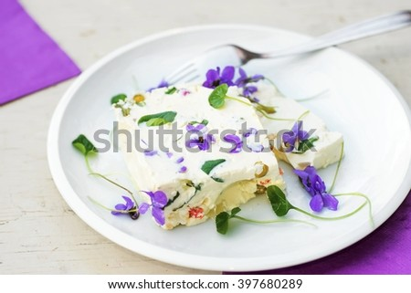 Whipped gelatin cream with vegetable and egg and edible blooming spring flower, spring and easter traditional food - stock photo