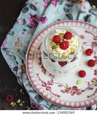 Whipped ice cream dessert with white chocolate, fresh raspberry and chopped pistachios in a jar - stock photo