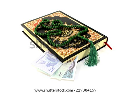 whipped Quran with Egyptian piastre before light background - stock photo