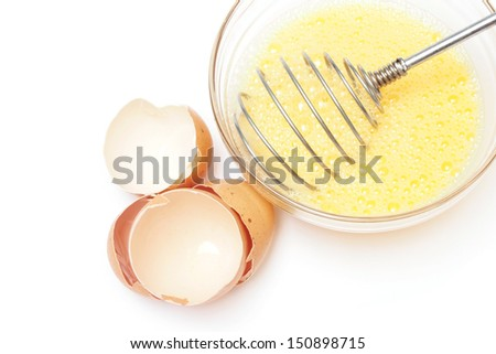 whisk and beaten eggs in a bowl on white background