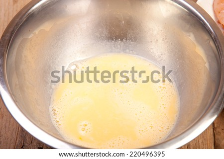 whisked egg in metal bowl on wooden table