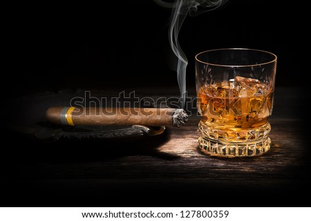 Whiskey and cigar on wooden background close up - stock photo
