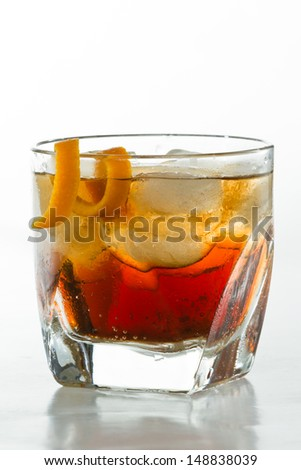 whiskey and cola cocktail served in a short glass garnished with an orange twist - stock photo
