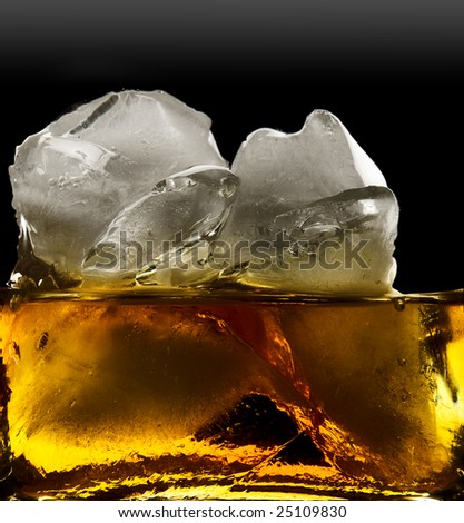 whiskey and ice,   ice isolated over a black background - stock photo
