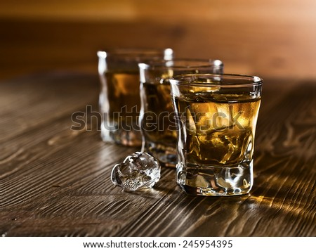 whiskey and natural ice on old wooden table - stock photo